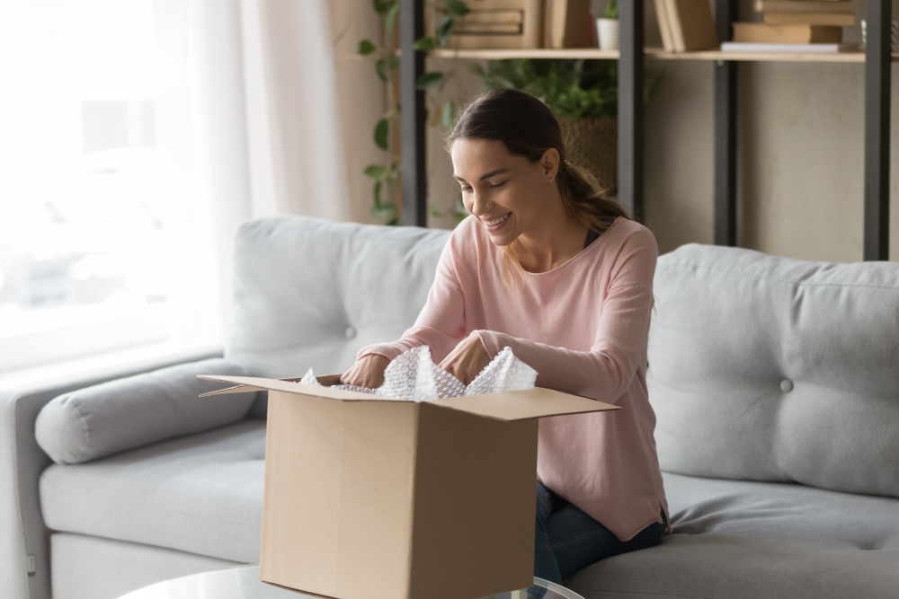 Shutterstock_1390237637 Happy woman sitting on couch at home opening carton box received parcel package from relatives or shopper make order internet website satisfied client, easy and fast service commerce delivery concept