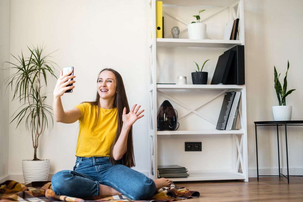 Shutterstock_1687992496 Phone video call. A young woman communicates via video, zoom. She is sitting on the floor in a Scandinavian style room.