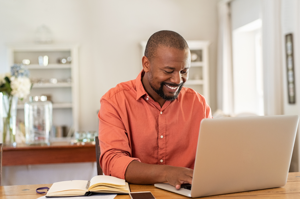 Shutterstock_1426545566 Smiling black man using laptop at home in living room. Happy mature businessman send email and working at home. African american freelancer typing on computer with paperworks and documents on table.