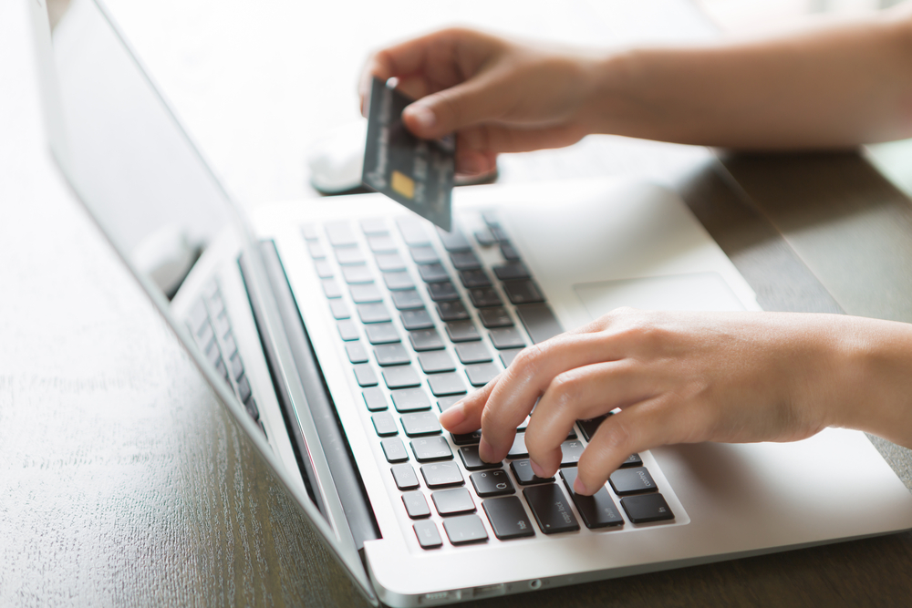 Shutterstock_229253272 Hands holding a credit card and using laptop computer for online shopping