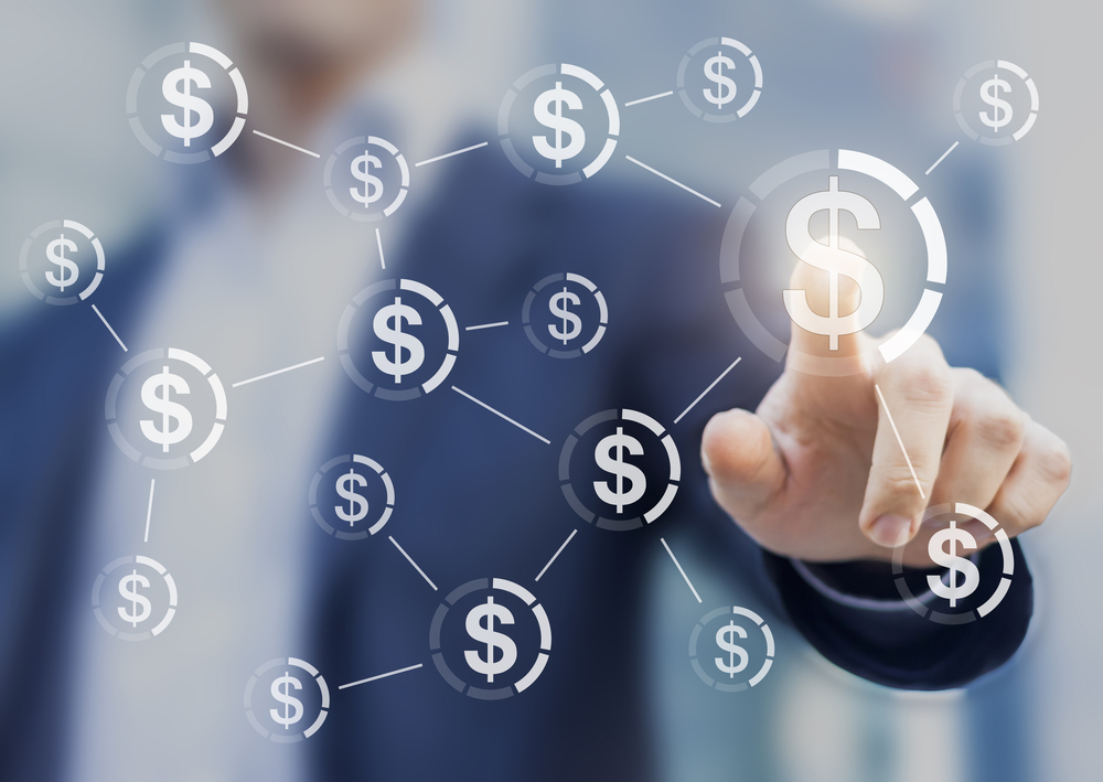 Shutterstock_465025475 Businessman touching button with dollar currency symbols connected in network, concept about global finance