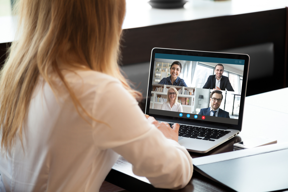 Shutterstock_1689337993  Back view of businesswoman speak using Webcam conference on laptop with diverse colleagues, female employee talk on video call with multiracial coworkers engaged in online briefing from home