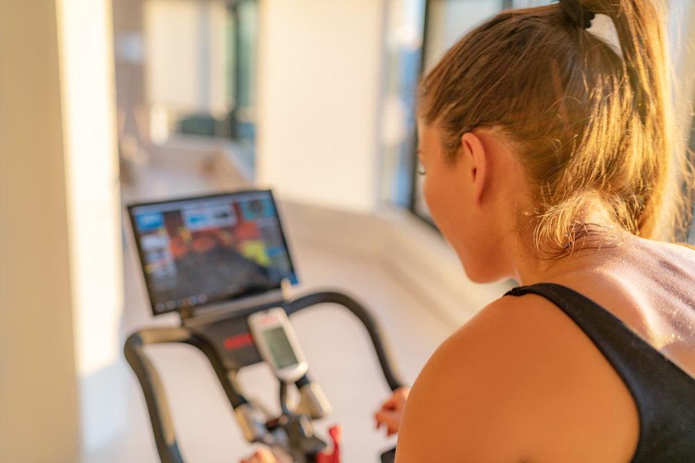 Shutterstock_1538639102 Fitness workout woman training at home on smart stationary bike equipment connected online live streaming class indoors for biking exercise. Indoor cycling. Focus on the sweat on person's back.