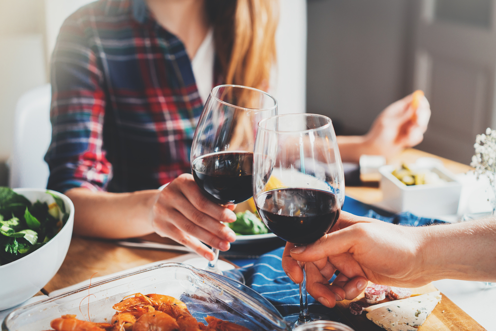 Shutterstock_604422317 Happy romantic couple celebrating engagement, best friends making cheers with glasses of red wine while dinning at cozy home atmosphere, traditional and holidays concept