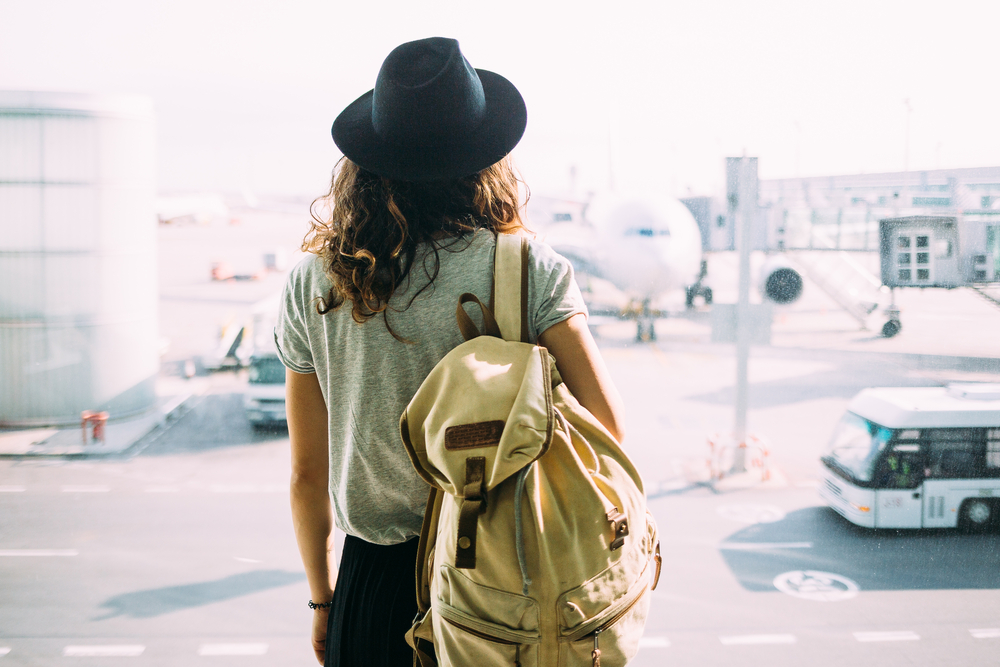 Shutterstock_572624629 Girl in hat with backpack traveling in the airport