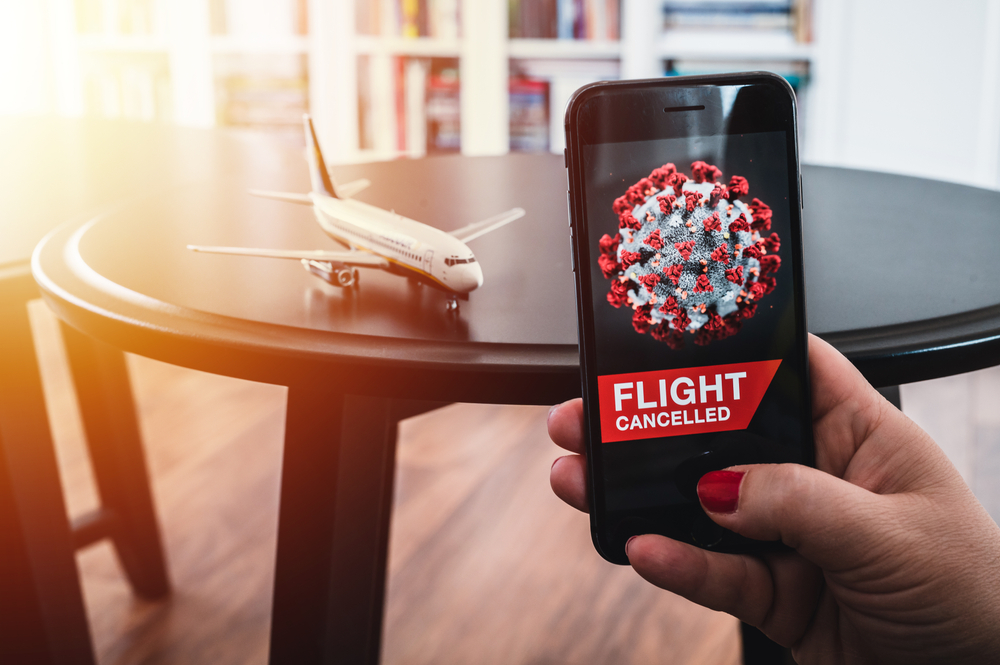 Shutterstock_1676951800 Airplane and flight cancellation. Flight cancelled. Pandemic of coronavirus. Coronavirus 2019 COVID-19 theme. Coronavirus with flight cancelled wallpaper on smartphone. Scale model airplane by phone.