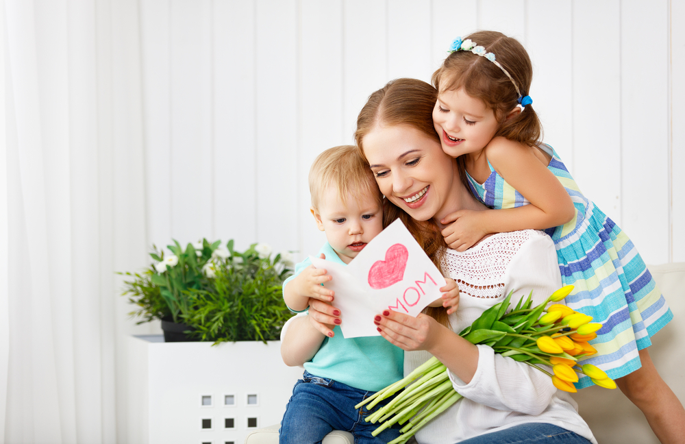 Shutterstock_608950949 Happy mother's day! Children congratulates moms and gives her a postcard and flowers tulips