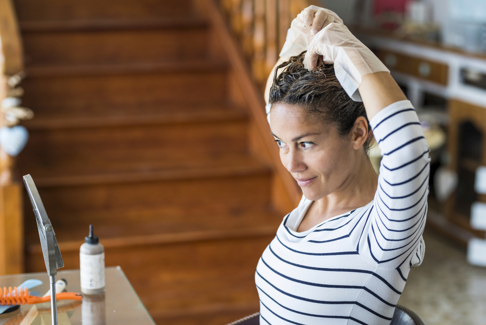 Shutterstock_1675618384 Home made hair dye at home for beauty young caucasian woman looking at the mirror - stay at home concept for coronavirus emergency worldwide pandemic contagion