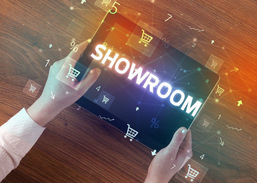 Shutterstock_1688546533 Close-up of a hand holding tablet with SHOWROOM inscription, online shopping concept