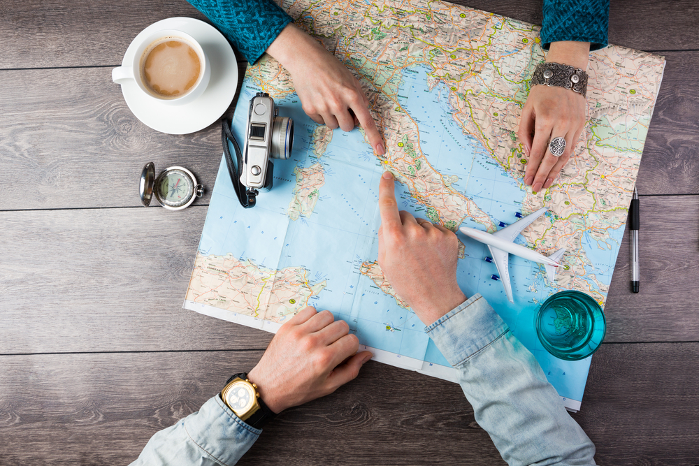 Shutterstock_293482145 Young couple planning honeymoon vacation trip with map. Top view. Pointing to Europe Rome