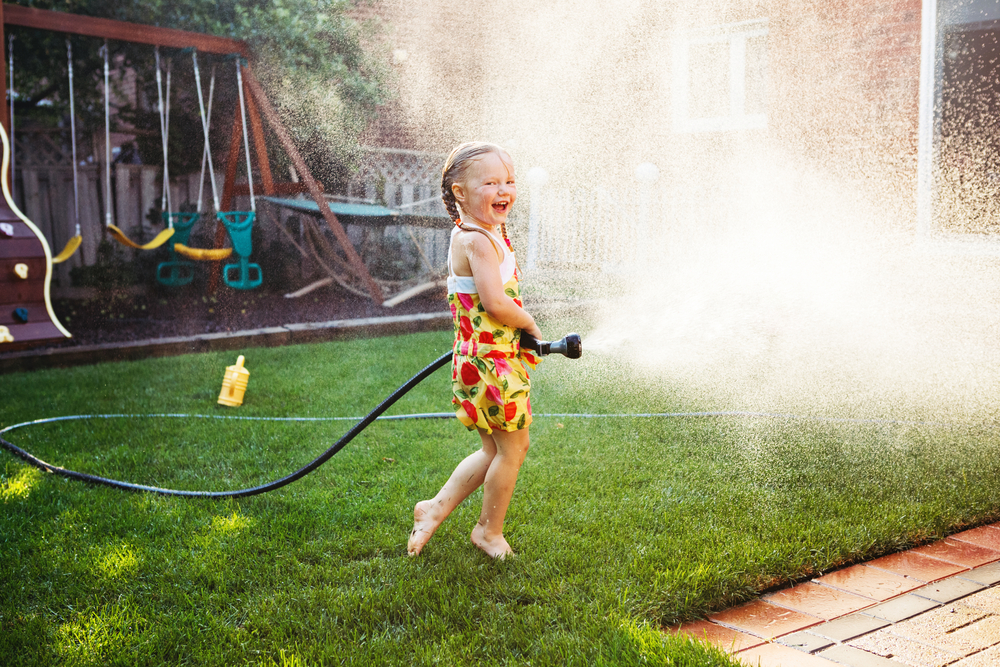Shutterstock_685423807 One girl splashing with gardening house on backyard on summer day. Child playing with water outside at sunset. Candid moment, lifestyle home kid activity.