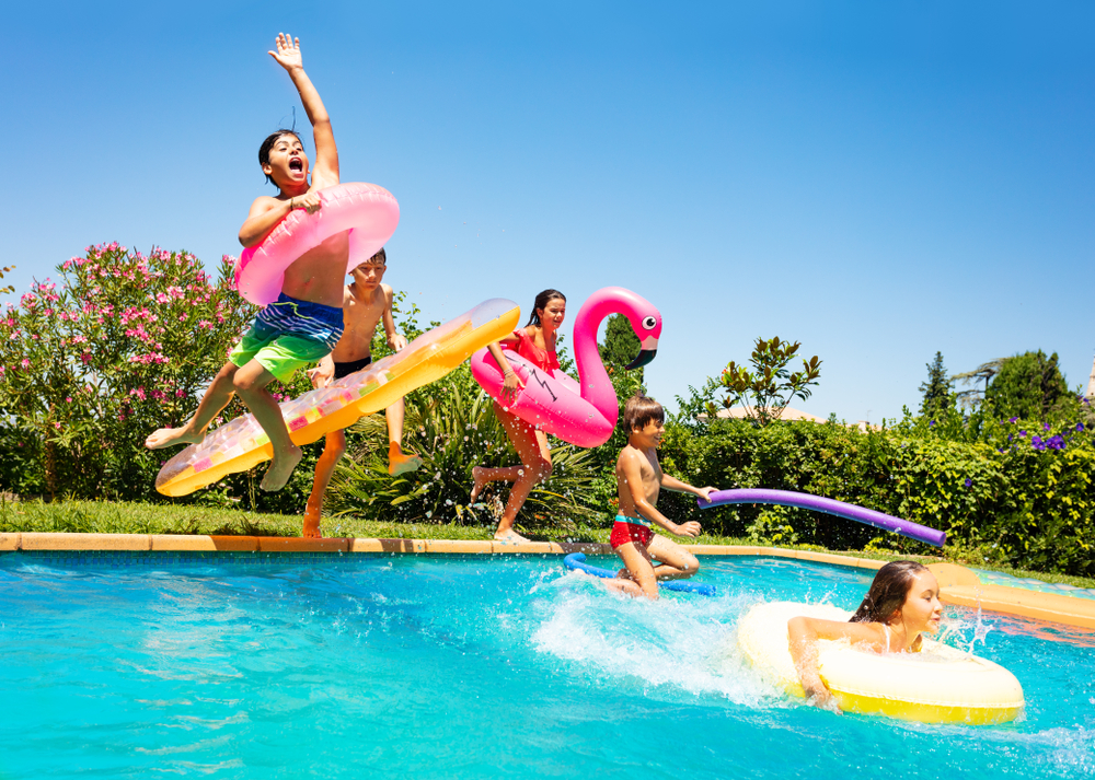 Shutterstock_1240262632 Happy friends jumping in pool on the vacations