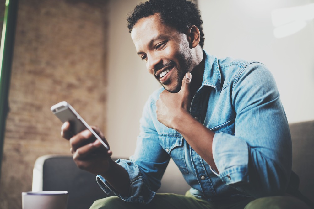 Shutterstock_562748479 Happy bearded African businessman using phone while sitting on sofa at his modern home.Concept of young people working mobile devices.Blurred background