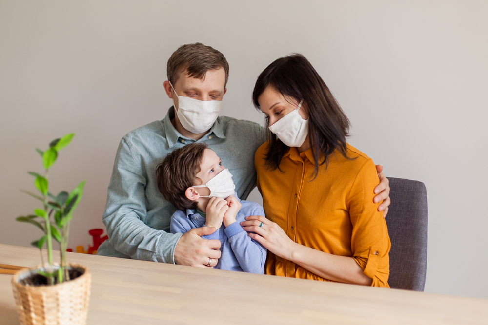Shutterstock_1679839444 Young modern quarantined coronavirus family in medical masks. The call to stay home stop the pandemic. Self-isolation together is the solution. Care covid-19. mom dad son millennials