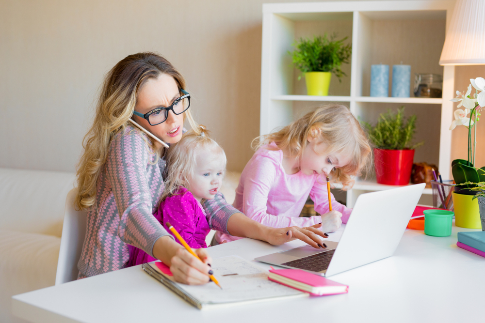 Shutterstock_1070125520 Busy woman trying to work while babysitting two kids