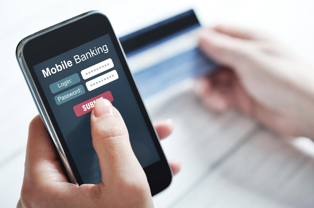 Shutterstock_177915332 Female hands using mobile banking on smart phone