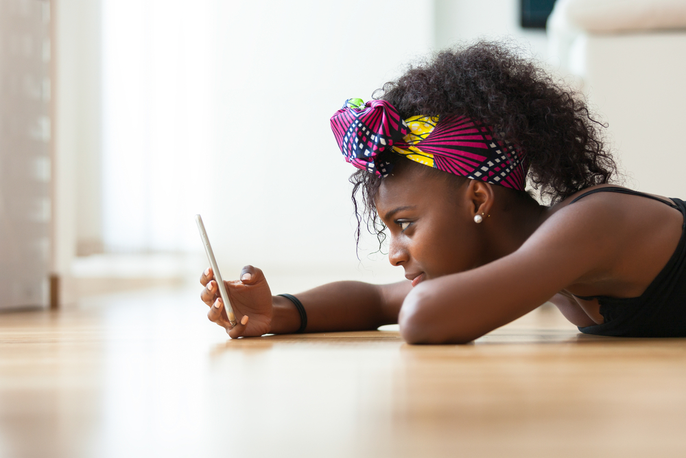 Shutterstock_323884478 African American woman sending a text message on a mobile phone - Black people