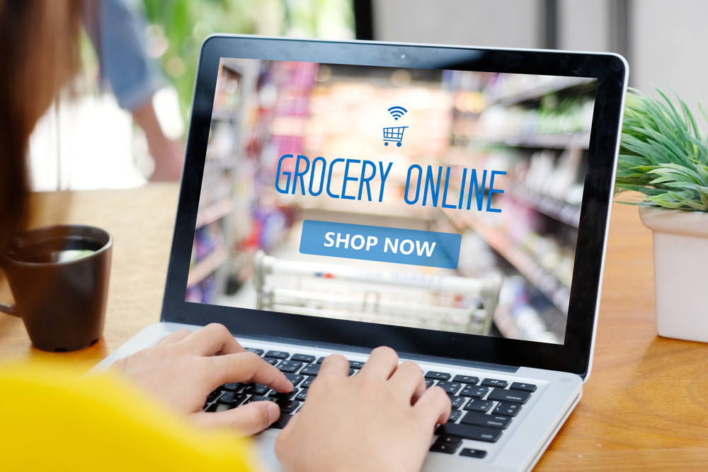 Shutterstock_758218510 Grocery online shop to order food delivery from supermarket, Woman hands using laptop computer for shopping grocery store online, electronic marketing, e commerce business concept