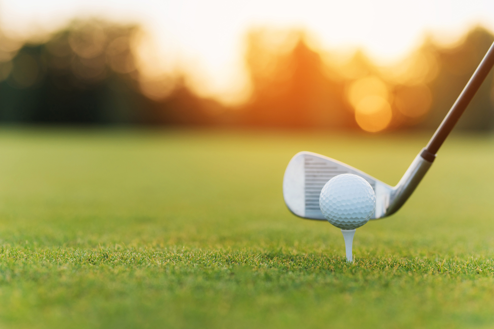 Shutterstock_727560205 Close up. Stylish metal golf club and golf ball on a stand, against a sunset background. Low angle