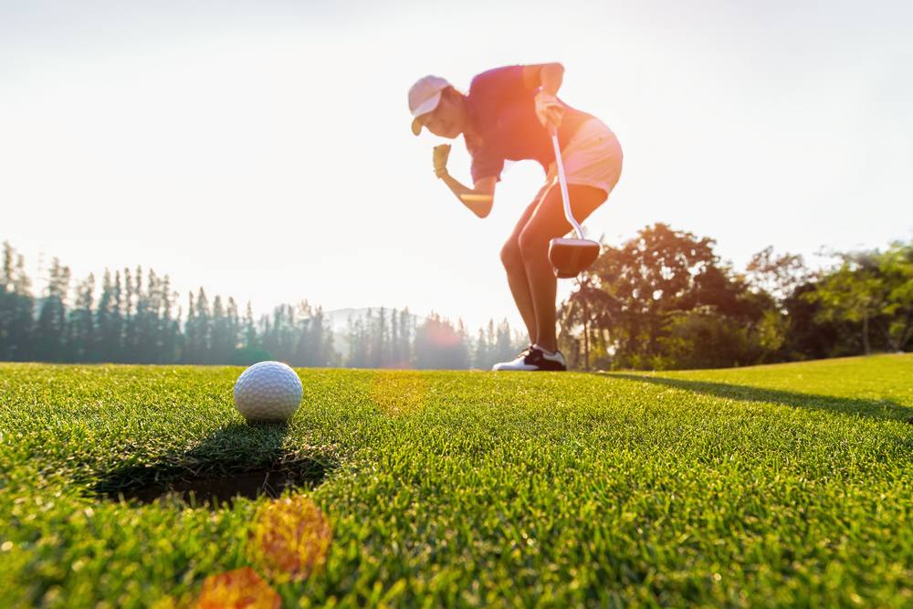 Shutterstock_789754279 Sport Healthy. Golfing game. Asian ladies woman golfer action to win after winner long putting golf ball on the green golf, outdoors sunset time, copy space. Healthy Concept