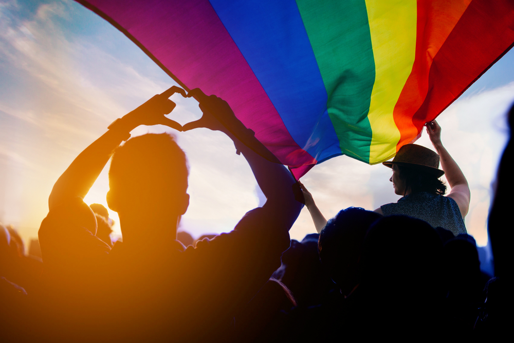 Shutterstock_1177679803 Pride community at a parade with hands raised and the LGBT flag.