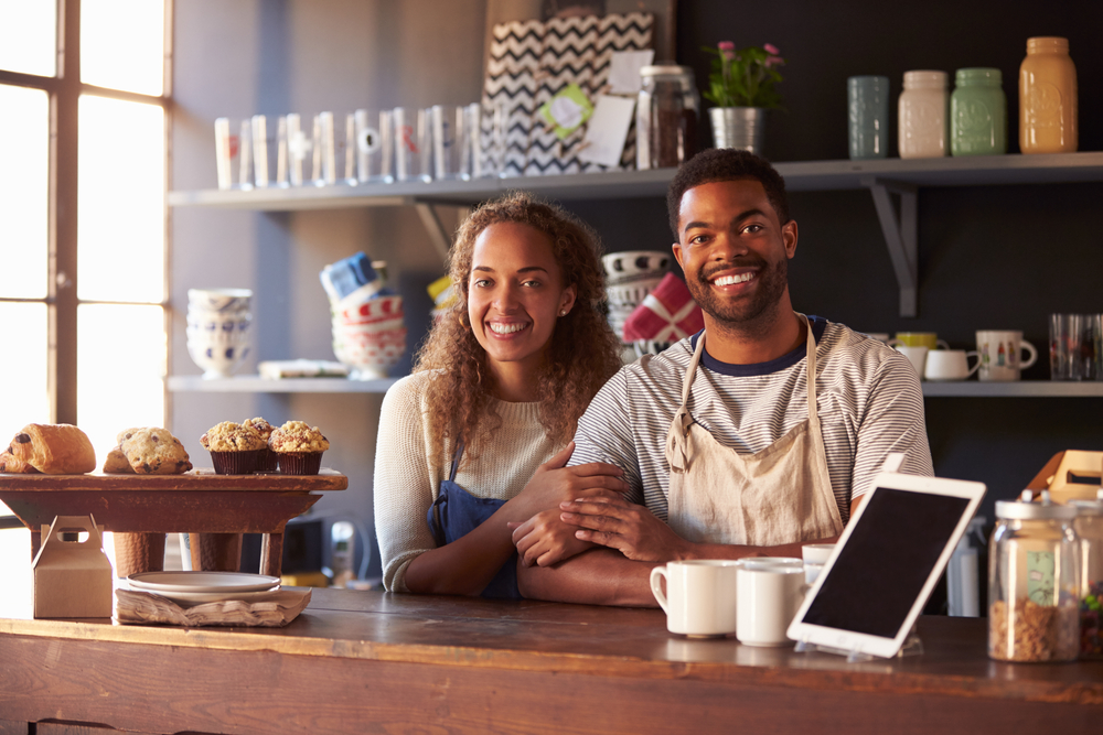Shutterstock_372379228 Portrait Of Couple Running Coffee Shop Behind Counter