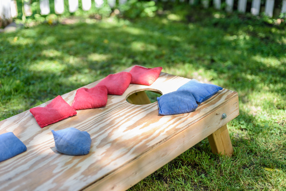 Shutterstock_717048250 red and blue bags on homemade wood cornhole board