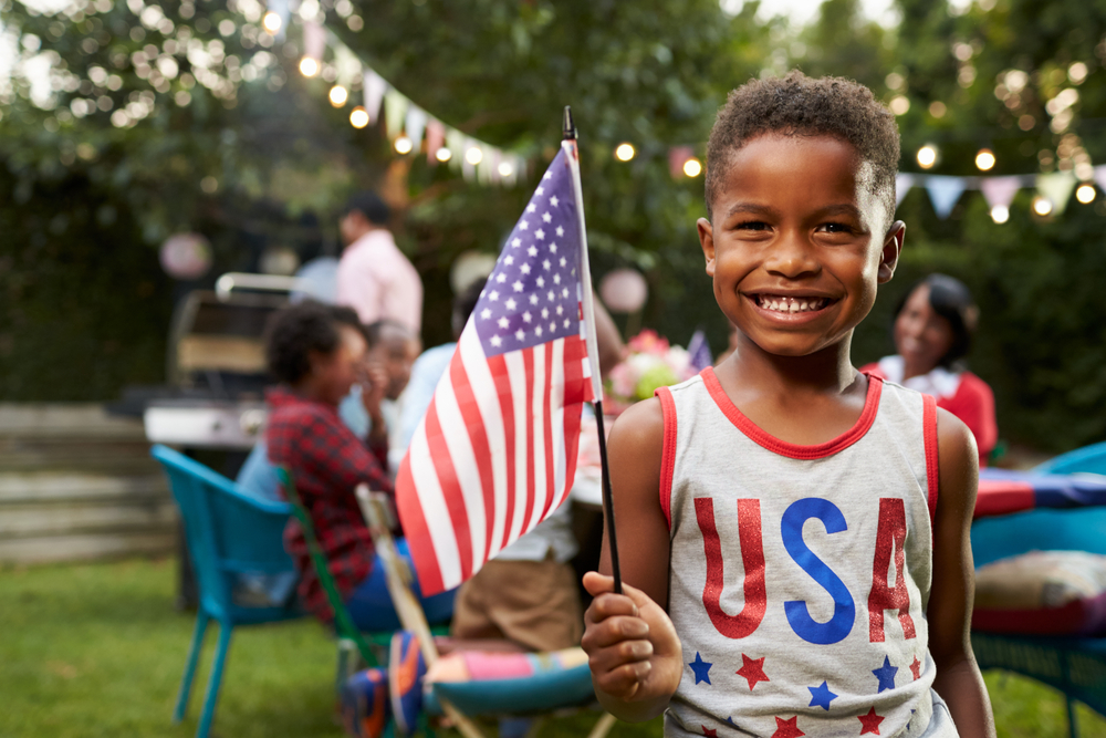 Shutterstock_555281659 Young black boy holding flag at 4th July family garden party