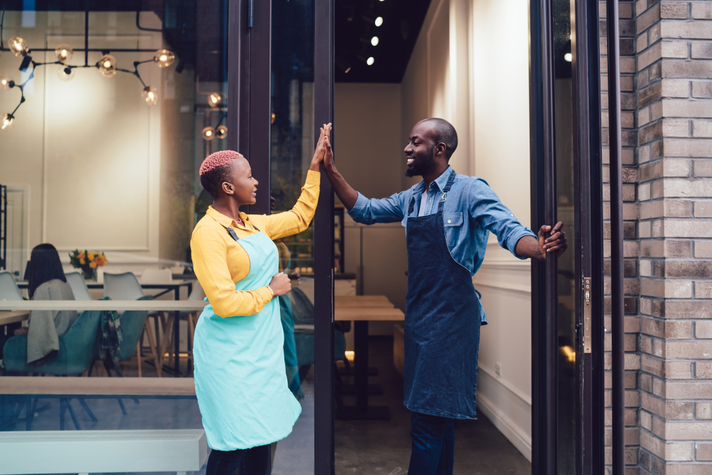 Shutterstock_1590751882 Joyful business partners in uniform looking at each other and giving high five while standing on entrance of own cafe and celebrating successful start