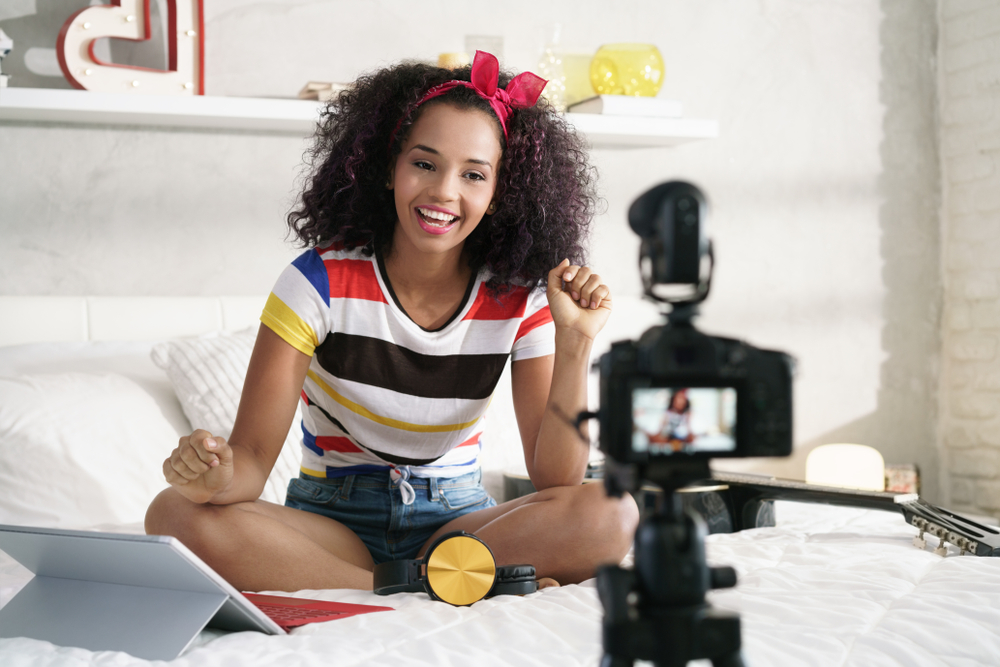 Shutterstock_1094656709 Happy girl at home speaking in front of camera for vlog. Young black woman working as blogger, recording video tutorial for Internet