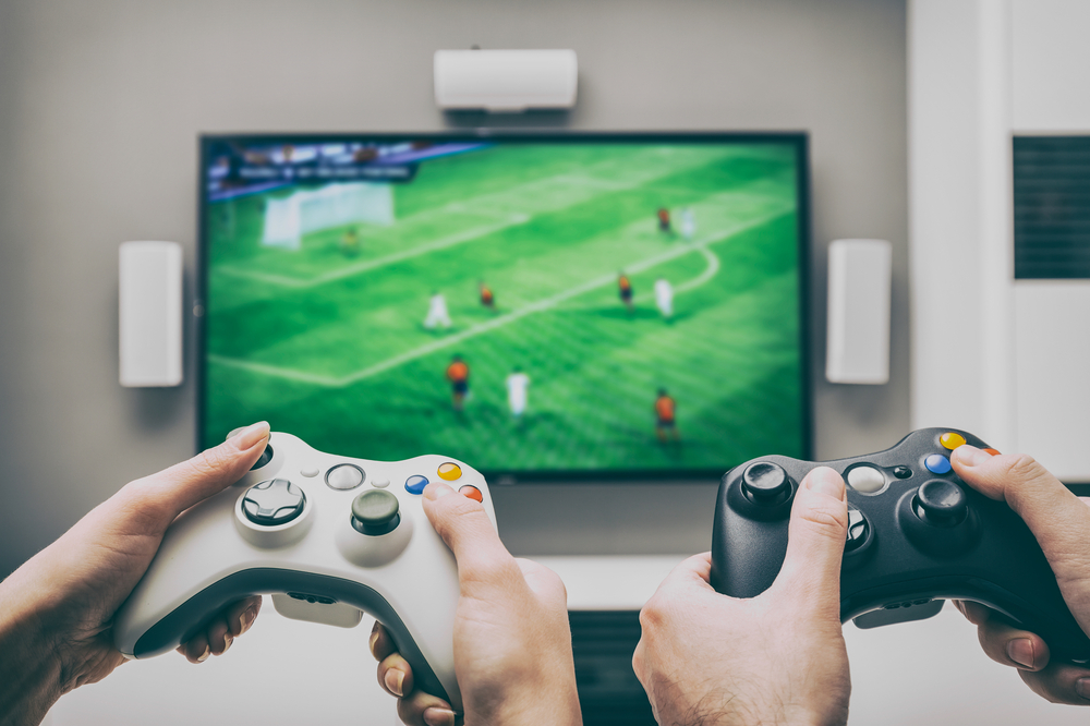 Shutterstock_537529714 gaming game play tv fun gamer gamepad guy controller video console playing player holding hobby playful enjoyment view concept - stock image