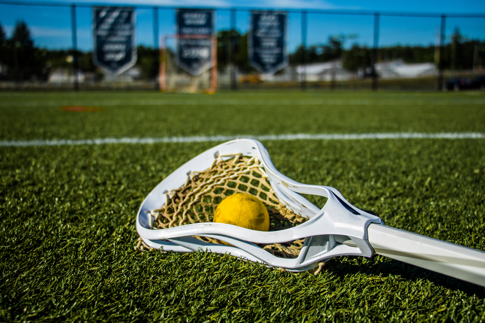Shutterstock_661312372 Single yellow lacrosse ball on the grass front of a training net