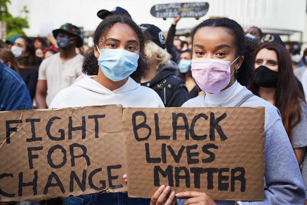 "Shutterstock_1746891338 Vancouver BC, Canada, May 31 2020: Portrait of two young women of dark skin colour with a face mask holding cardboard banners ""black lives matter"""