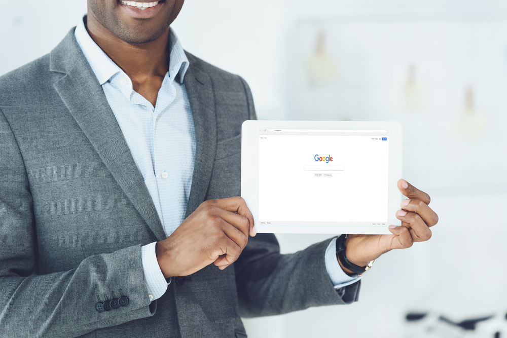 Shutterstock_786959593 cropped image of smiling man showing tablet with loaded google page