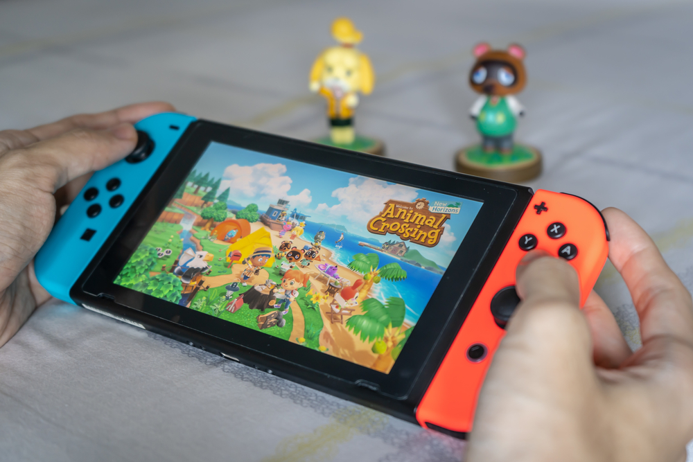 Shutterstock_1711683874 Bangkok, Thailand - March 21, 2020 : A man playing Animal Crossing on Nintendo Switch.