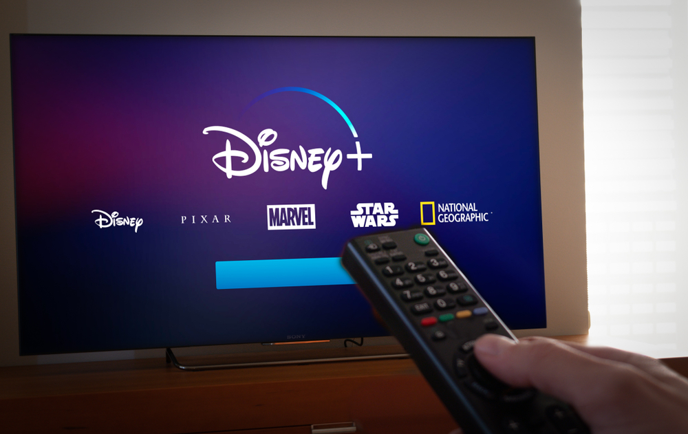 Shutterstock_1272496885 Barcelona, Spain. Jan 2019: Man holds a remote control With the new Disney+ screen on TV. Disney+ is an online video streaming subscription service.Illustrative
