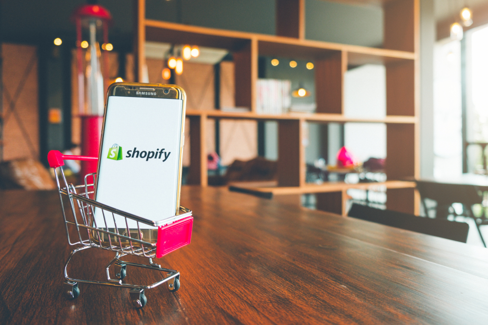 Shutterstock_1134002783 CHIANG MAI,THAILAND - July 7,2018: Mobile Phone using Shopify app on the screen in shopping cart on wooden table.