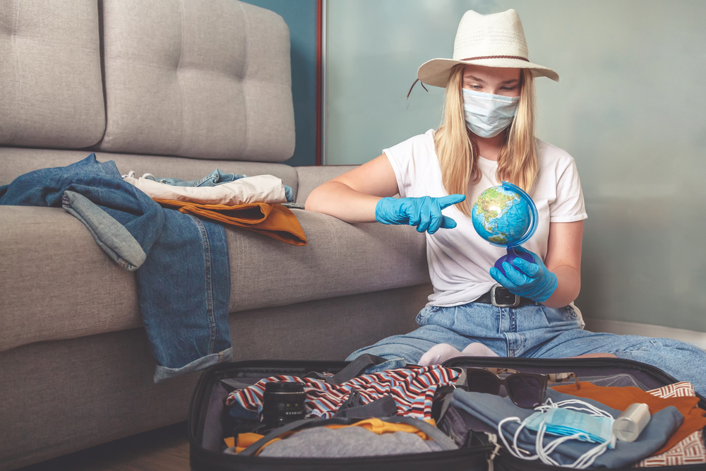 Shutterstock_1767283199 Travel. masked girl puts her things in a suitcase and dreams of rest, traveling after quarantine, blocking, covert 19. Staycation.local travel.Tourism after opening borders, end of quarantine