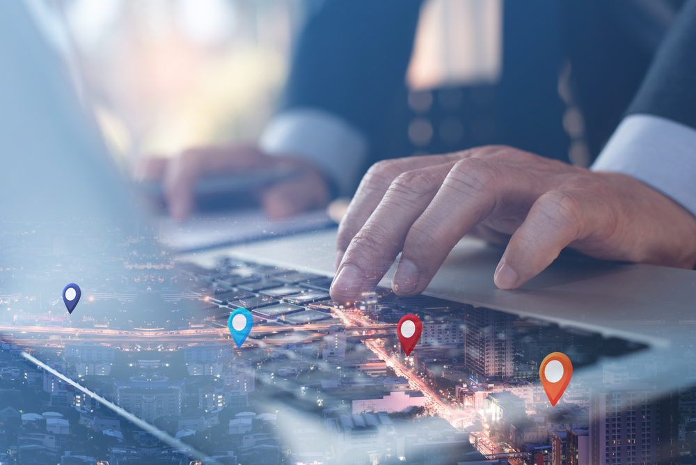 Shutterstock_1771141148 GPS map, pin address location on mobile apps. Double exposure of man hand using laptop computer searching target place on night cityscape. Business and technology, marketing plan concept