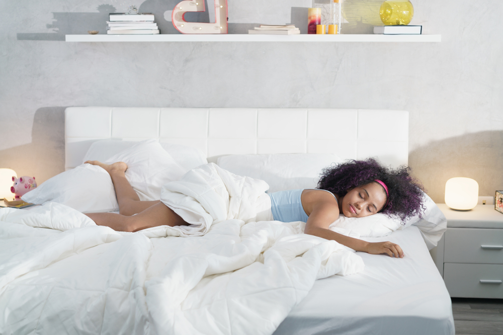 Shutterstock_1091314463 Young African American woman waking up at home. Portrait of happy black girl smiling, enjoying a large king size mattress all for herself.