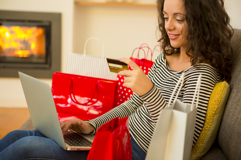 Shutterstock_325949822 Beautiful woman at home at the warmth of the fireplace, shopping online
