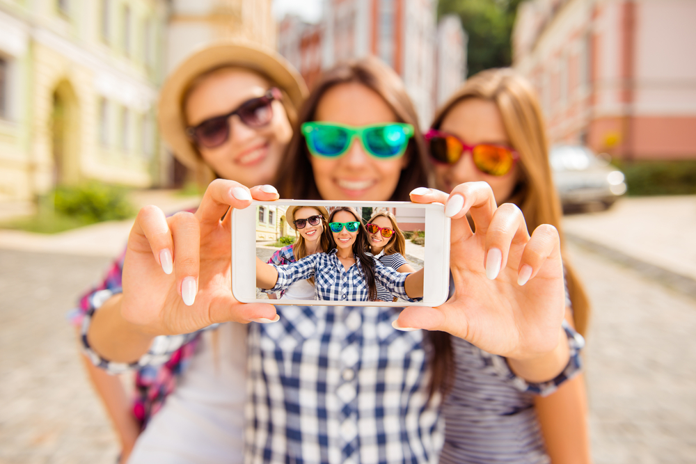 Shutterstock_531501235 Three happy best girlfriends in glasses making selfie on smartphone.