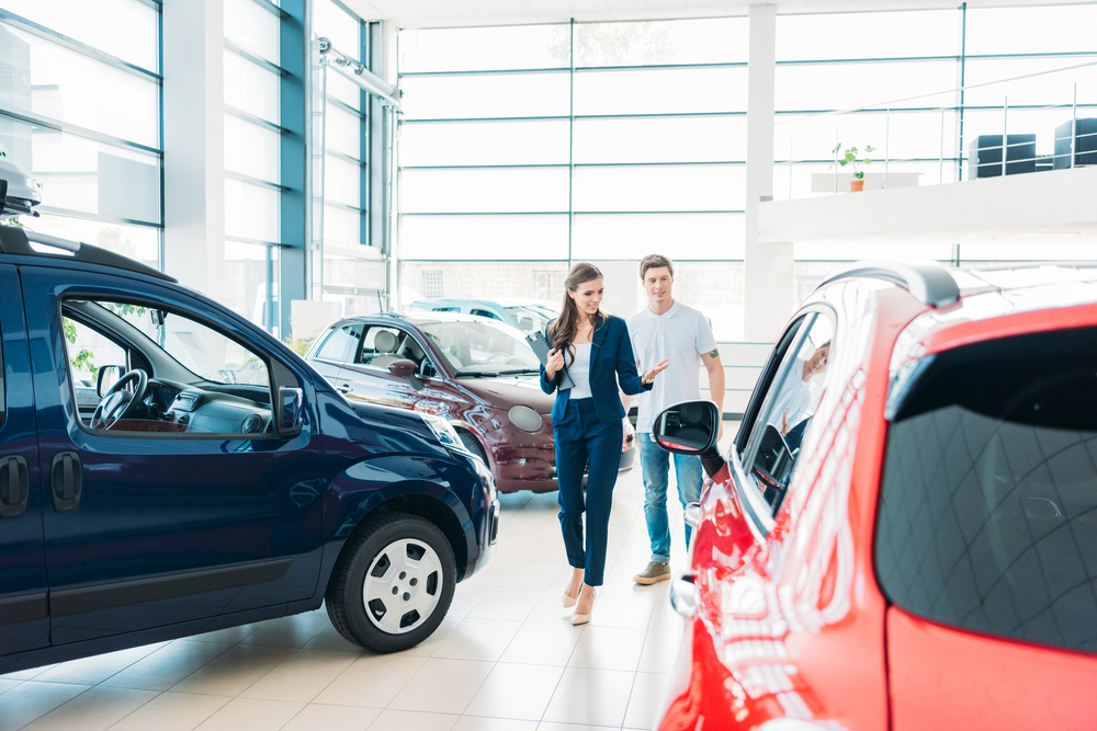 Shutterstock_746933677 female sales manager showing red car to the customer in showroom