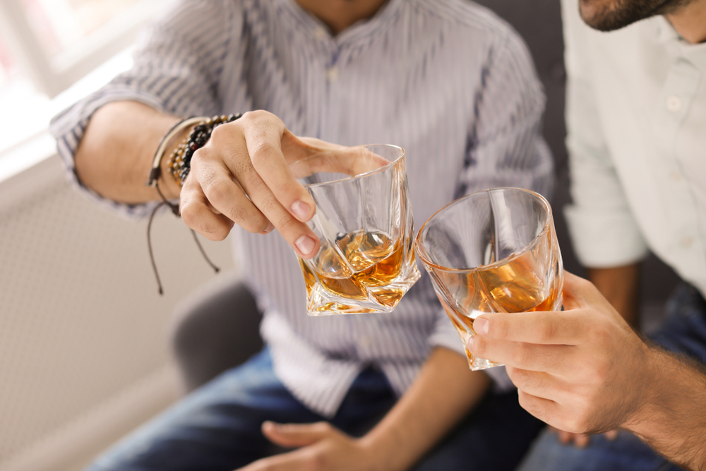 Shutterstock_1250604211 Friends toasting with glasses of whiskey indoors, closeup