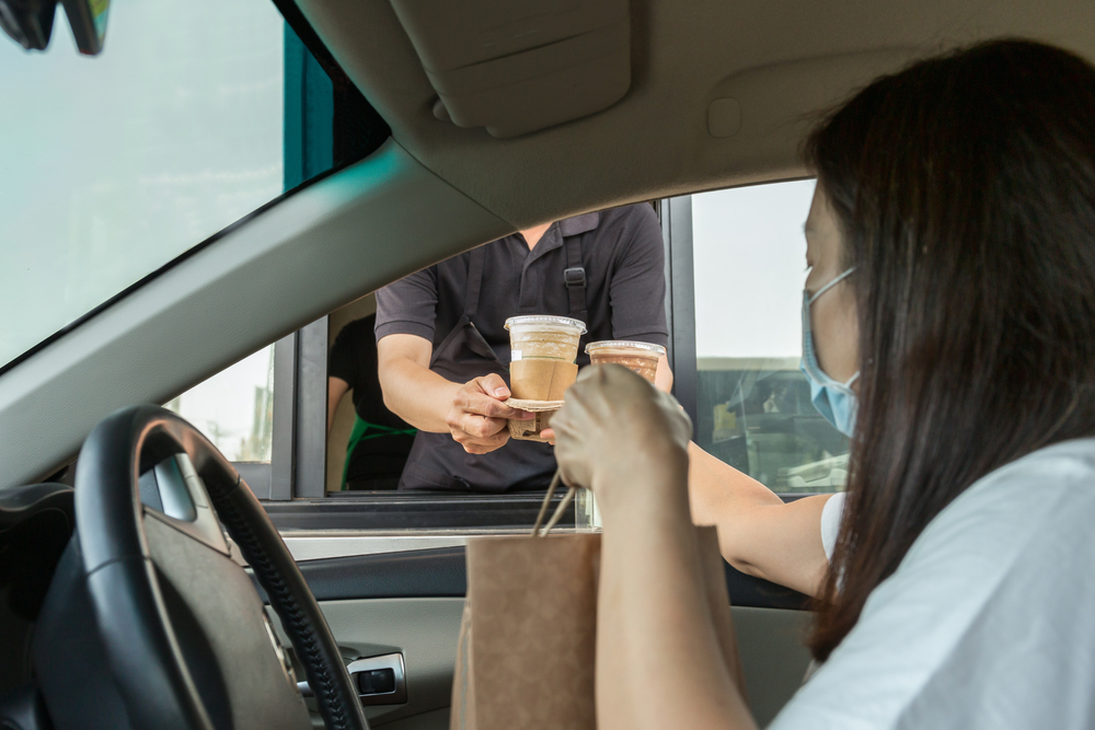 Shutterstock_1698492634 Woman in protective mask taking coffee at drive thru during coronavirus outbreak
