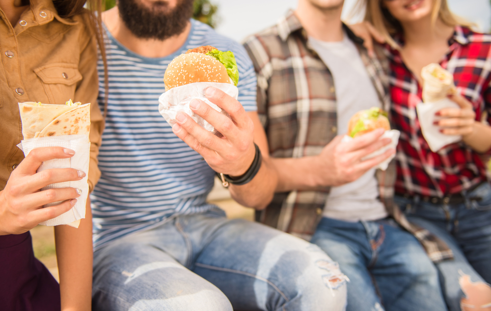 Shutterstock_321206387 Young people walking outdoors. Sitting in the park and eat fast food