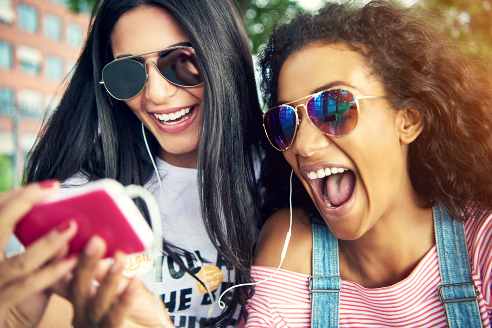 Shutterstock_567601909 Female friends wearing sun glasses and smile widely as they take a photo with their cell phone