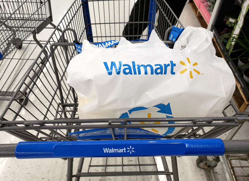 Shutterstock_1450023608 MONTREAL, CANADA - APRIL 30, 2019: Branded Walmart shopping cart and bag in Walmart store. Walmart is an American retail corporation that operates a chain of hypermarkets and discount department store