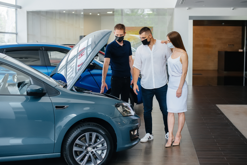 Shutterstock_1771930034 Young couple in masks selects a new vehicle and consult with a representative of the dealership in the period of the pandemic. Car sales, and life during the pandemic
