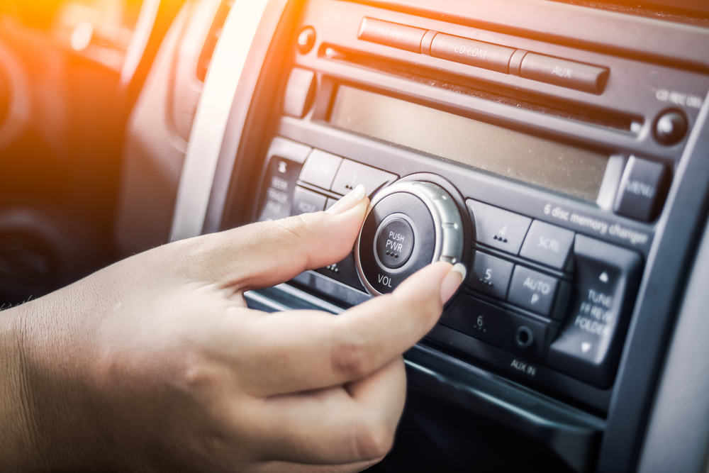 Shutterstock_486390466 woman turning button of radio in car